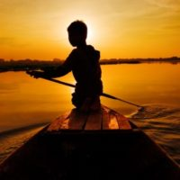 7428477 - silhouette of boy paddling boat at sunset